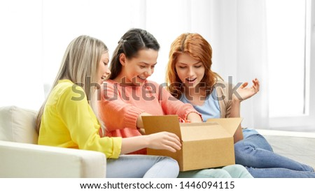 delivery and friendship concept - three teenage girls or friends opening parcel box at home #1446094115