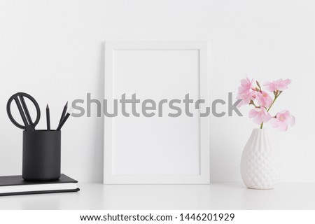 White frame mockup with pink oleander in a glass vase and workspace accessories on a white table.Portrait orientation. #1446201929