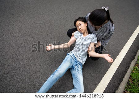 Sick little child girl with epileptic seizures outdoor,daughter suffering from illness with epilepsy during seizure attack,asian young woman or mother care of girl patient,brain,nervous system concept #1446218918