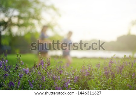 Image blur two women are running for exercise in the park. There is a scene in front of a purple flower. #1446311627