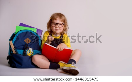 Children go back to school. Little happy  girl doing homework at home with backpack full of books, pencils. Pupil reading a book, writing and painting.  Kid is drawing. Child in glasses.  #1446313475