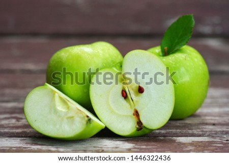 Whole,sliced and half of Green Apple(Malus pumila) on wooden table with blurred background.Sweet,sour and freshness taste.Have a lot of fiber, vitamins and minerals.Food,Fruits or healthcare concept. #1446322436
