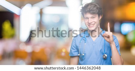 Young doctor wearing medical uniform over isolated background showing and pointing up with finger number one while smiling confident and happy. #1446362048