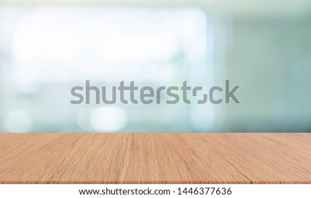 abstract blurred opening big window with natural light in living room background with modern brown color wood tabletop perspective for show,promote,ads on display design #1446377636