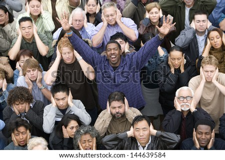 Portrait of a happy African American man raising hands while people covering their ears #144639584