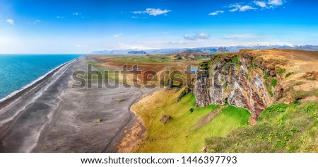 View of Kirkjufjara black sand beach from Dyrholaey promontory on Atlantic South Coast.