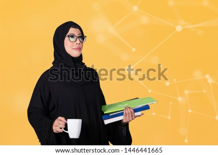 Arab woman student holding books and a cup. Isolated on colored background. Arabic education concept.