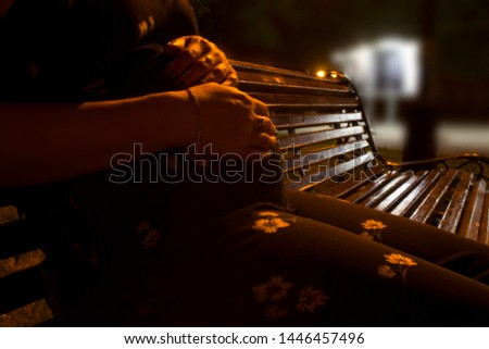 A pregnant girl is sitting on the evening on a bench in the city center.  #1446457496