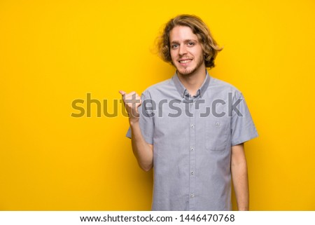 Blonde man over isolated yellow background pointing to the side to present a product #1446470768