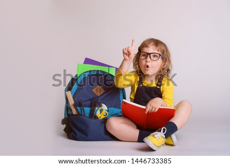 Children go back to school. Little happy  girl doing homework at home with backpack full of books, pencils. Pupil reading a book, writing and painting.  Kid is drawing. Child in glasses.  #1446733385