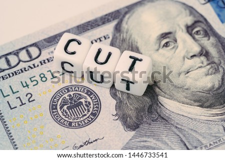 FED, Federal Reserve with interest rate cut concept, small cube block with alphabet building the word CUT next to Federal Reserve emblem on US Dollar banknote. Royalty-Free Stock Photo #1446733541