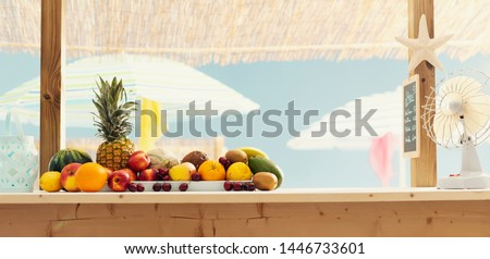 Beach bar kiosk with delicious fresh fruit on the counter and colorful umbrellas in the background, summertime concept #1446733601
