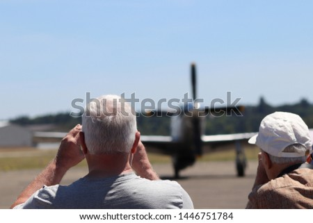People in a crowd watch an airshow.