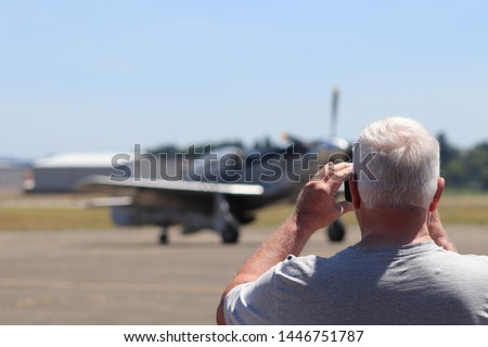 People in a crowd watch an airshow.  Vintage plane in soft focus as a crowd photographs and watches an airshow in the summer.  Happy People gather as an airshow is enjoyed.