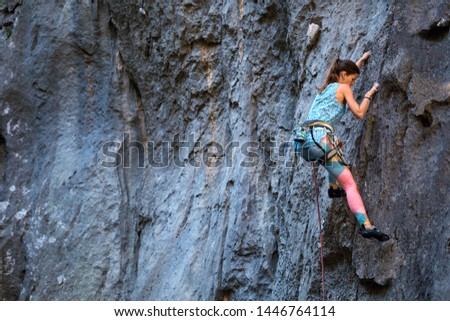 Climber overcomes challenging climbing route. A girl climbs a rock. Woman engaged in extreme sport. Extreme hobby. #1446764114