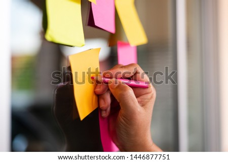 Close up woman hand writing colorful note sticky for brainstorm and share idea strategy workshop business.Brainstorming concept. #1446877751