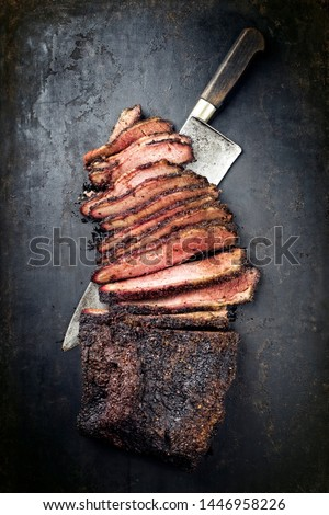 Traditional smoked barbecue wagyu beef brisket offered as top view with knife on an old rustic board with copy space  #1446958226