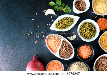Composition of dry legumes. Assortment of colorful legumes in bowls. Lentils, Moth beans, Mung Beans, Masoor or red lentils, Split Chickpea, Toor Dal, Raw Split Mung Bean Lentils, Yellow Split. #1446976247