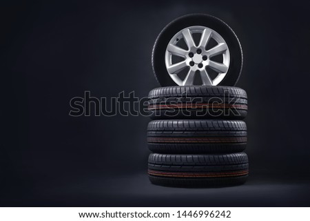 New tires pile on a dark background. Tire fitting background. Copy space.  #1446996242