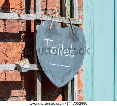 Toilet Sign hanging on door.