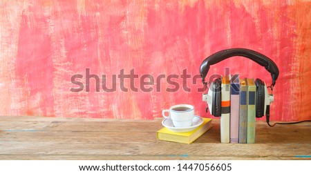 audio book concept with book, headphones and cup of coffee, panorama format on grungy background, good copy space