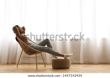 Weekends Finally! Relaxed Girl Sitting on Modern Chair near Window, Enjoying Morning #1447143434