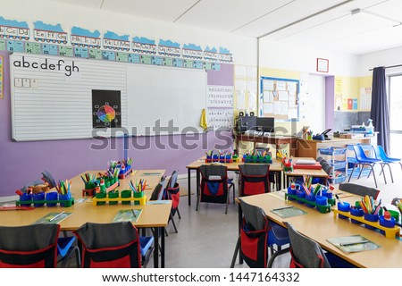 Empty Classroom In Elementary School With Whiteboard And Desks Royalty-Free Stock Photo #1447164332