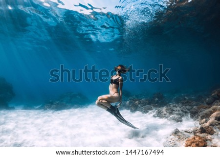 Woman freediver posing over sandy sea with fins. Freediving in Hawaii #1447167494