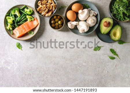 Ketogenic diet ingredients for cooking dinner. Raw salmon, avocado, broccoli, bean, olives, nuts mushrooms, eggs in ceramic bowls. Grey texture background. Flat lay, copy space #1447191893