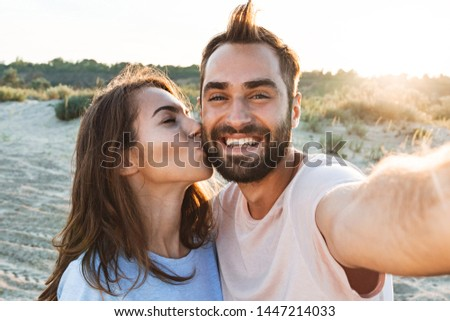 Beautiful young smiling couple spending time at the beach, embracing while taking a selfie, kissing on a cheek