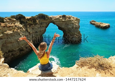 Young beautiful woman enjoying the panoramic top view of rocky beaches with cliffs somwhere, somwhere in Algarve, Portugal. Atlantic ocean shore background. Copy space for text. #1447217624