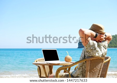 Fit travel blogger sitting at beach bar writing article on white laptop. Freelance remote work concept. Self employed man coding, wearing typical tourist shirt and hat. Copy space, sea view background #1447217633