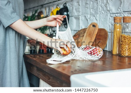 Young woman in the grey dress pulls apples out of knitted rag bag string bag shopper in the kitchen, zero waste, slow life Royalty-Free Stock Photo #1447226750