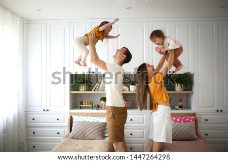 Beautiful Caucasian family with two children in their arms, dad and mom hold two children in the air, a real bright Scandinavian-style interior #1447264298