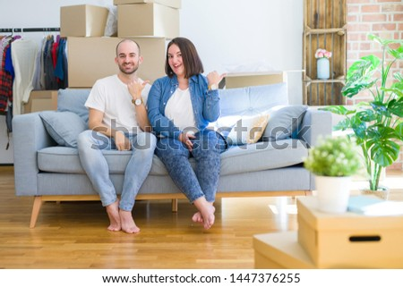 Young couple sitting on the sofa arround cardboard boxes moving to a new house smiling with happy face looking and pointing to the side with thumb up. #1447376255