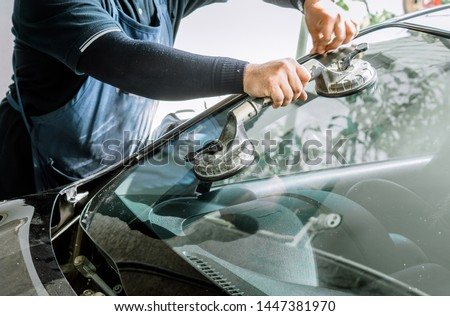 Mechanics man changing the broken windshield and automobile windshield or windscreen replacement of white car in Auto Repair Shop Royalty-Free Stock Photo #1447381970