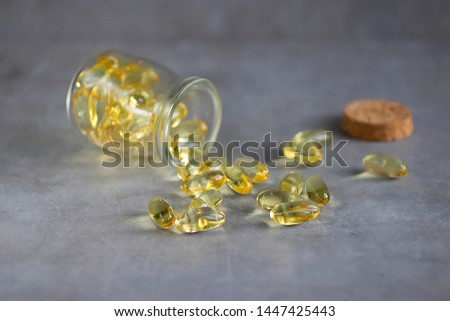 Yellow transparent gelatin capsules on a gray background. Omega-3, Omega-6, Omega-9 fatty acids. The concept of medicine and pharmacology. Soft focus. #1447425443