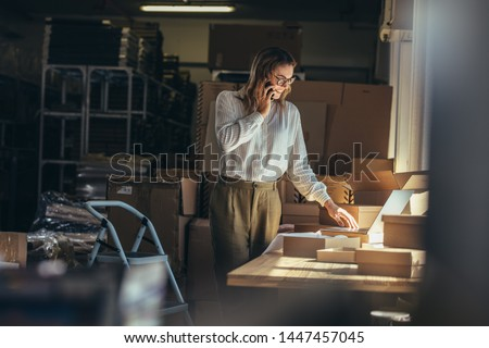 Female online seller confirming orders from customer on the phone. Online web store owner taking order on phone. Royalty-Free Stock Photo #1447457045