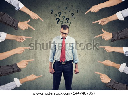 Concept of accusation. Sad man with questions looking down with many fingers pointing at him  Royalty-Free Stock Photo #1447487357