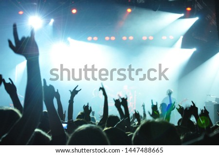 A crowd of people dancing at a musical rock concert under the light and smoke of spotlights #1447488665