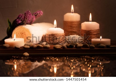 Spa decorative set with sea pebbles, salt, aromatic candles, towel and flower. Golden composition in low key, dark photo with beautiful reflections and bokeh. With space for text.