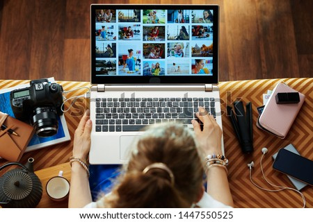 Upper view of stylish woman sitting on couch in the modern living room looks at image library while transferring photos from DSLR photo camera on a laptop.
