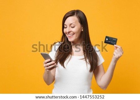 Portrait of smiling young woman in white casual clothes using mobile phone, holding credit bank card isolated on yellow orange wall background in studio. People lifestyle concept. Mock up copy space #1447553252