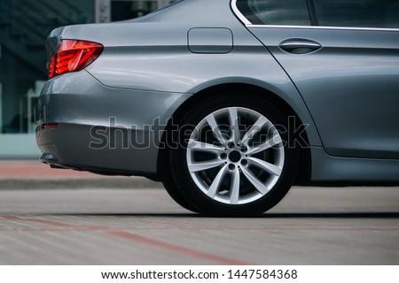Modern sedan car rear wheel and rim Royalty-Free Stock Photo #1447584368