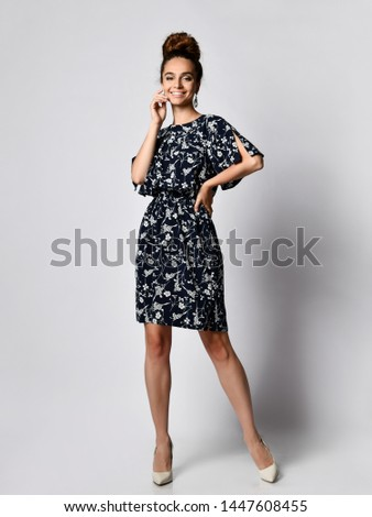 Slim curly female model in a silk pale dark dress looking at the camera in full growth. . Cute girl in romantic clothes is going on a date, smiling pretty on a white background. #1447608455