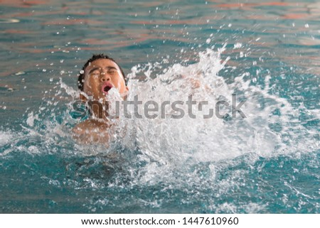 young boy splashing in swimming poll,  #1447610960