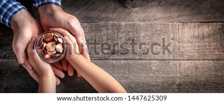 Hands Of Father Giving Jar Of Coins To Child On Wooden Table Background - Inheritance / Parent Providing For Children Concept Royalty-Free Stock Photo #1447625309