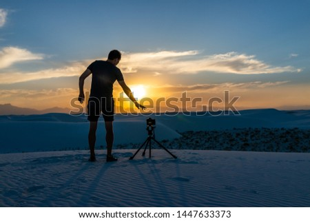 Man photographer with tripod doing time lapse photography with camera in white sands dunes national monument in New Mexico view of sunset #1447633373