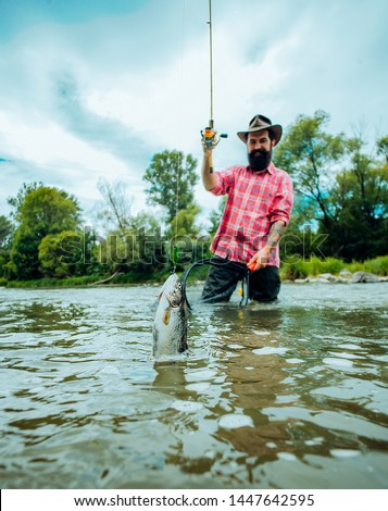 Fly fishing for trout. Fishing in river. Catches a fish. Catching a big fish with a fishing pole. Fly fishing - method for catching trout #1447642595