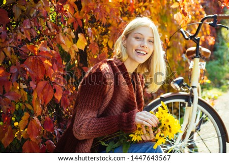 Autumn woman in autumn park with red pullover. Beautiful Autumn Woman with Autumn Leaves on Fall Nature Background. Pretty tenderness model looking at camera #1447643567